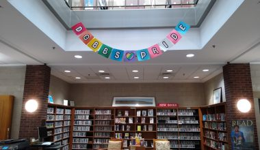 """""""Dobbs Pride"""" written out on individual squares of colored paper to resemble the pride and trans pride flags, hanging over the new books section on the first floor of the library."""